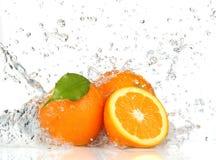 Frutta ed acqua arancioni di spruzzatura fotografia stock