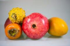 Frutta esotica, cachi, mango, pitahaja, melograno su un fondo bianco - Immagine Stock