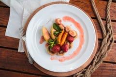Frutta fiammeggiata sul piatto bianco Immagine Stock