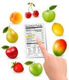 Frutta fresca con i fatti etichetta e mano di una nutrizione Fotografie Stock