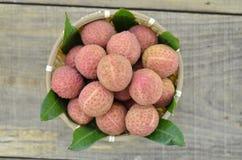 Frutta fresca del litchi in canestro di bambù su fondo di legno Fotografie Stock Libere da Diritti