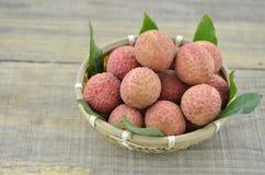 Frutta fresca del litchi in canestro di bambù su fondo di legno Immagini Stock
