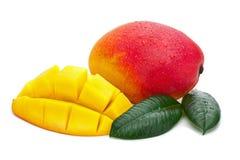Frutta fresca del mango con il taglio e foglie verdi isolate sulle sedere bianche Immagini Stock