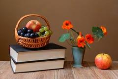 Frutta fresca in del vimine, dei libri e dei fiori del canestro Immagini Stock Libere da Diritti