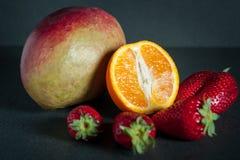 Frutta fresca (mango, arancia, fragole) su un fondo scuro immagine stock libera da diritti