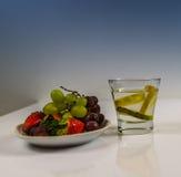 Frutta fresca su un piattino bianco con acqua con il limone Immagini Stock