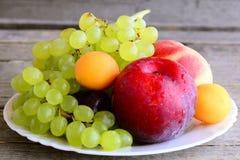 Frutta fresca su un piatto bianco e su un vecchio fondo di legno Le pesche mature, le prugne, le albicocche, uva si ramificano Al Fotografie Stock Libere da Diritti