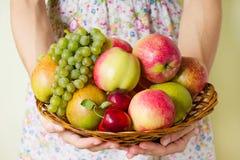 Frutta matura fresca su un piatto di legno di vimini nelle mani di una giovane donna Raccolto di autunno dei frutti Fotografie Stock Libere da Diritti