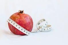 Frutta rossa fresca del melograno e nastro di misurazione Immagine Stock Libera da Diritti