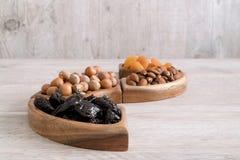 Frutta secca e dadi in ciotole di legno sulla tavola Forma di Wave fotografia stock