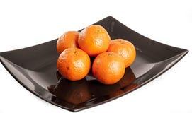 Frutta subtropicale Mucchio dei mandarini delle arance sul piatto del plack e sul fondo bianco isolato dello studio Fotografie Stock