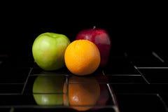 Frutta sulle mattonelle nere Fotografia Stock