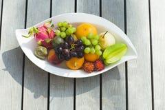 Frutta tropicale su un piatto bianco su una superficie di legno fotografia stock libera da diritti