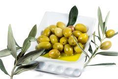 Frutta verde oliva e foglie inzuppate in olio d'oliva Immagine Stock Libera da Diritti