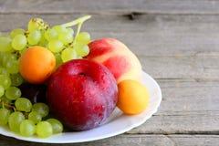 Frutti crudi su un piatto bianco e su un fondo di legno d'annata Le pesche dolci, le prugne, le albicocche, uva si ramificano Cib Fotografia Stock Libera da Diritti