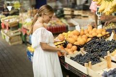 Frutti d'acquisto della giovane donna sul mercato fotografia stock