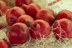 Frutti del melograno con paglia sul mercato Immagini Stock Libere da Diritti