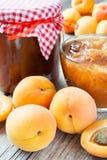 Frutti dell'albicocca e barattolo maturi di inceppamento sulla tavola Immagini Stock