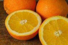 Frutti delle arance e fetta arancio sulla Tabella di legno e sul retro tessuto Fotografia Stock Libera da Diritti