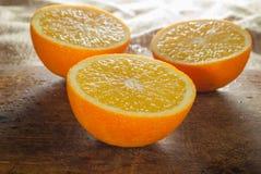 Frutti delle arance e fetta arancio sulla Tabella di legno e sul retro tessuto Immagini Stock Libere da Diritti