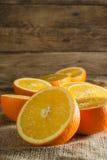 Frutti delle arance e fetta arancio sulla Tabella di legno e sul retro tessuto Immagine Stock Libera da Diritti