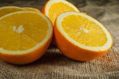 Frutti delle arance e fetta arancio sulla Tabella di legno e sul retro tessuto Immagini Stock