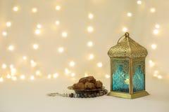 Frutti delle date e della lanterna davanti al fondo del bokeh Immagini Stock