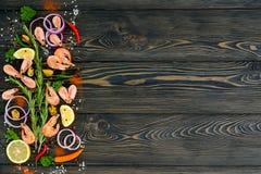 Frutti di mare con le verdure e le erbe su fondo di legno scuro Vista da sopra Spazio per testo Immagine Stock
