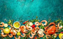 Frutti di mare crudi freschi - gamberetti e granchi con le erbe e le spezie sul fondo del turchese Copi lo spazio fotografia stock