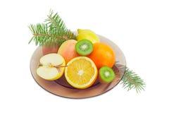 Frutti differenti su un piatto di vetro e sui rami dell'abete Fotografie Stock