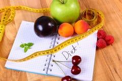 Frutti e centimetro con il taccuino, il dimagramento e l'alimento sano Fotografie Stock Libere da Diritti