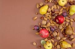 Frutti e dadi di autunno su fondo marrone con lo spazio della copia Immagini Stock Libere da Diritti
