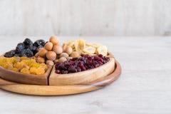 Frutti e dadi secchi in ciotole di legno sulla tavola immagine stock