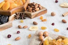 Frutti e dadi secchi in ciotole di legno sulla tavola fotografia stock