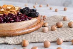 Frutti e dadi secchi in ciotole di legno sulla tavola Con la nocciola fotografia stock