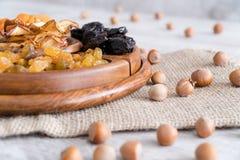 Frutti e dadi secchi in ciotole di legno sulla tavola Con le nocciole intorno fotografie stock libere da diritti