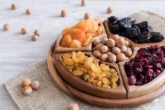 Frutti e dadi secchi in ciotole di legno sulla tavola Con le nocciole intorno fotografia stock