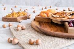 Frutti e dadi secchi in ciotole di legno sulla tavola Con le nocciole intorno immagini stock libere da diritti