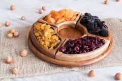 Frutti e dadi secchi in ciotole di legno sulla tavola Con le nocciole intorno fotografia stock libera da diritti