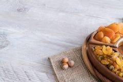 Frutti e dadi secchi in ciotole di legno sulla tavola con spazio libero per testo fotografia stock