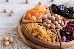 Frutti e dadi secchi in ciotole di legno sulla tavola dettaglio immagine stock
