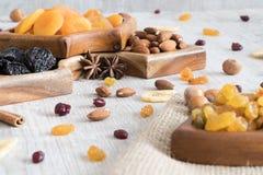 Frutti e dadi secchi in ciotole di legno sulla tavola Lotto dei dadi, dei frutti e dell'anice stellato intorno fotografia stock