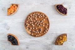Frutti e dadi secchi in ciotole di legno sulla tavola Negli angoli e nel mezzo immagine stock