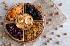 Frutti e dadi secchi in ciotole di legno sulla tavola Vista superiore immagine stock