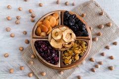 Frutti e dadi secchi in ciotole di legno sulla tavola Vista superiore immagini stock libere da diritti
