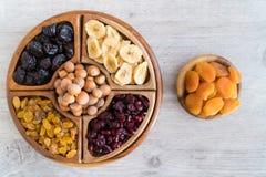 Frutti e dadi secchi in ciotole di legno sulla tavola Vista superiore fotografia stock