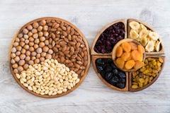 Frutti e dadi secchi in ciotole di legno sulla tavola Vista superiore immagine stock libera da diritti