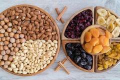 Frutti e dadi secchi in ciotole di legno sulla tavola Vista superiore immagini stock