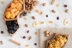 Frutti e dadi secchi in ciotole di legno sulla tavola Vista superiore fotografia stock libera da diritti