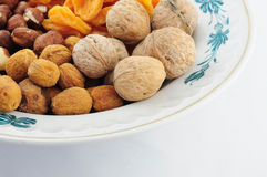 Frutti e dadi secchi sul piatto sulla cima sinistra Fotografia Stock